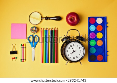 Back to school objects organized on yellow background. View from above - stock photo