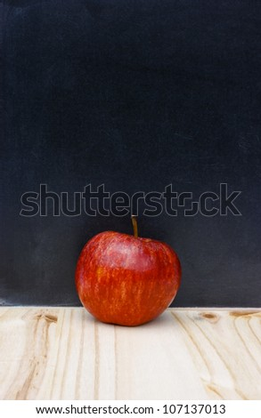 Back to school or college education concept. Red apple against a traditional authentic scratched blackboard or chalkboard. Copy space. - stock photo