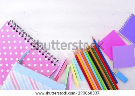 Back to School or Education Concept with stationery and desk accessories overhead on white wood rustic table with copy space for your text here. - stock photo