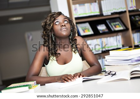 Back to School. Pretty teenage black african college student girl studying and reading a book in college library - stock photo