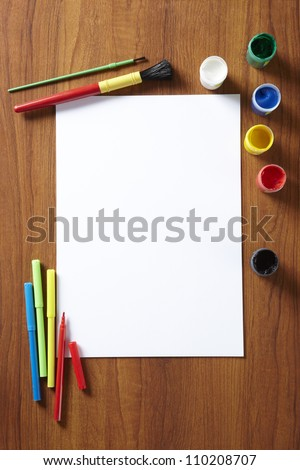Back to School pupils art pad paints and pens on wooden school desk from above - stock photo