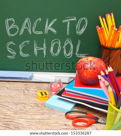 Back to school. School accessories against a school board. - stock photo