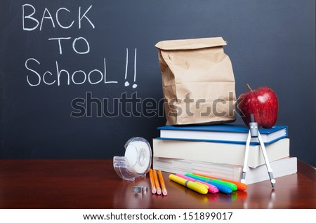 Back to school, school books with apple and  paper bag lunch on desk                                    - stock photo