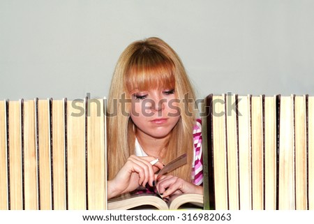 back to school - school girl surrounded by books reading a book. light grey back ground. - stock photo