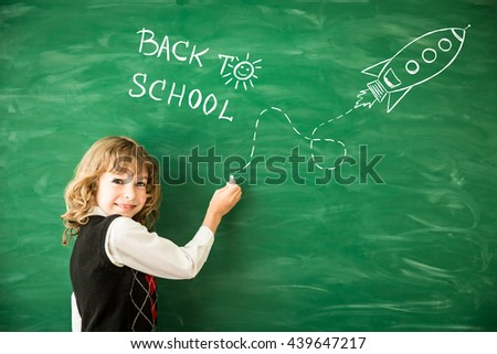 Back to school. Schoolchild in class. Happy kid against green blackboard. Child writing on chalkboard. School kid in classroom. Education and creativity concept - stock photo