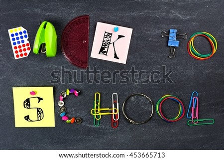 BACK TO SCHOOL spelled with school supplies against a blackboard background - stock photo