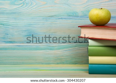 Back to school. Stack of colorful books on grunge blue green wooden background. Composition with vintage old hardback books, apple, pen, pencil,  Books stacking. Copy Space. Education background. - stock photo