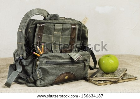 Back To School Theme. Retro Backpack And Apple On The Old Books - stock photo