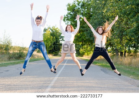 Back to school: three active beautiful young female students having fun jumping high on country road looking to camera on green trees copy space background - stock photo