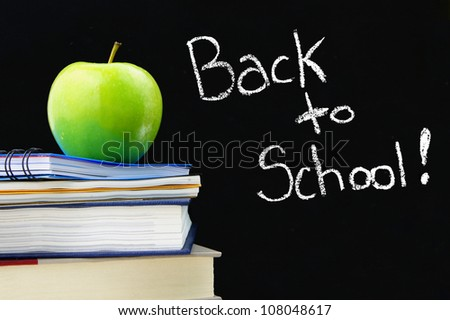 Back to School written on a blackboard with books and apple in front - stock photo