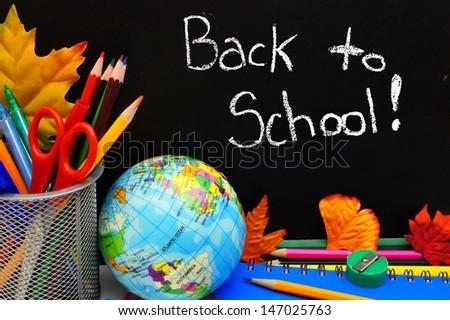 Back to School written on a blackboard with school supplies - stock photo