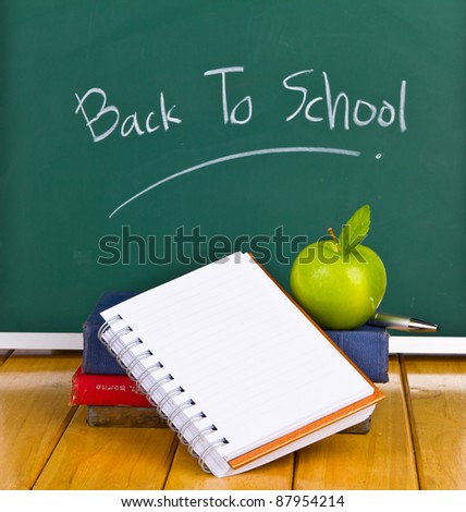 Back to school written on chalkboard with green apple and  books - stock photo