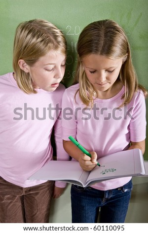 Back to school - 8 year old girls writing in notebook in classroom - stock photo