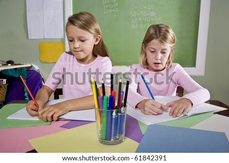 Back to school - 8 year old school girls in classroom writing in notebook - stock photo