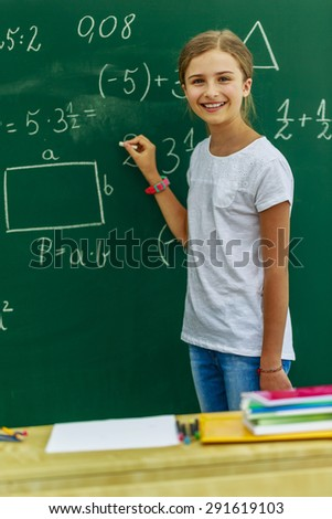 Back to school - young schoolgirl in the classroom - stock photo