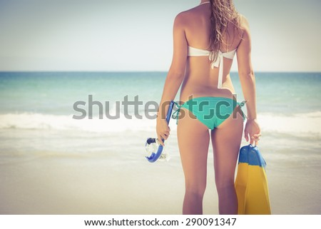 Back turned blonde holding scuba diving gear on the beach - stock photo