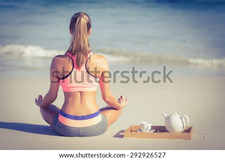 Back turned fit woman doing yoga on the beach - stock photo