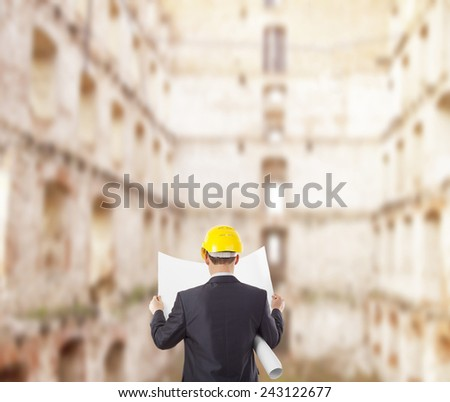 Back view architect look comparing blue print paper plan document housing project with building yellow helmet businessman stand round building many windows background Engineer with yellow helmet - stock photo