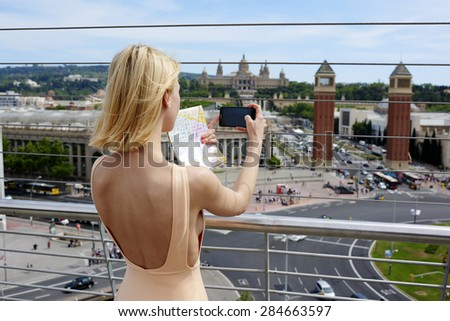 Back view attractive young female tourist taking picture of active life in the city with her smart phone camera, woman traveler photographing urban view with mobile phone, vacation holidays in summer - stock photo