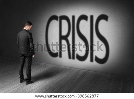 Back view businessman standing in front of concrete wall with shadow words crisis - stock photo