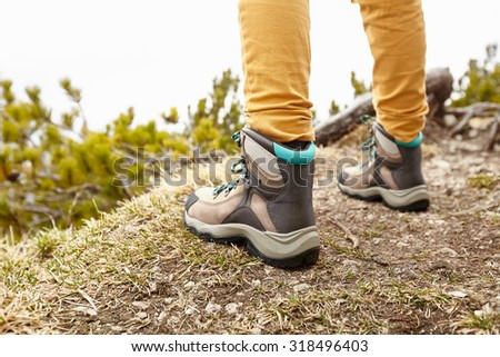Back view close up of woman wearing yellow pants and hiking boots outdoors - adventure concept - stock photo