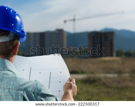 back view, closeup of male caucasian engineer at work looking at technical drawing plan - stock photo