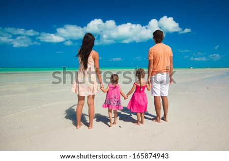Back view family of four on caribbean beach vacation - stock photo