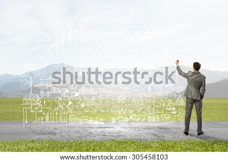 Back view image of businessman drawing sketches on wall - stock photo