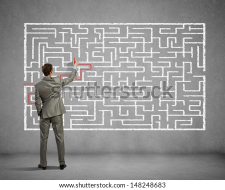 Back view image of young businessman trying to find way out of maze - stock photo