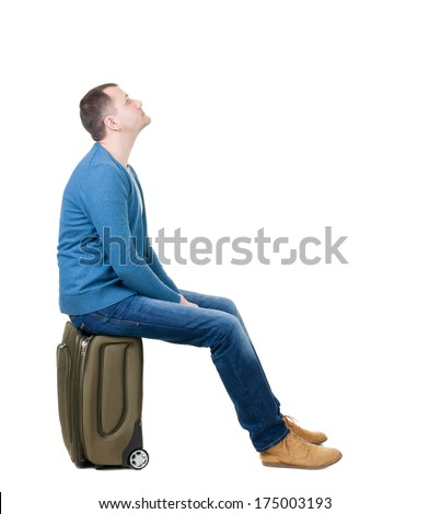 back view man sitting on suitcase. waiting at the station. backside view person.  Rear view people collection. Isolated over white background. guy with travel bag on wheels looking at something at top - stock photo