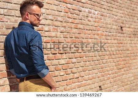 back view of a casual young man looking down with his hands in his pockets - stock photo