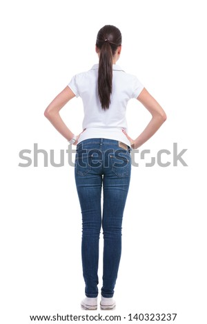 back view of a casual young woman standing with her hands on her hips. isolated on white background - stock photo