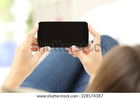 Back view of a close up of a woman hands watching media in a smart phone lying on a couch at home - stock photo