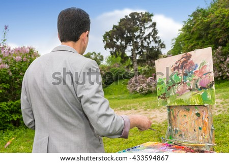 Back view of a concentrated male artist working  on a trestle and easel painting with oils and acrylics during an art class in a park - stock photo