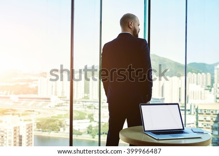 Back view of a confident man CEO is resting after meeting with staff company, while is standing near office window with view skyscrapers business center. Laptop computer with empty copy space screen - stock photo