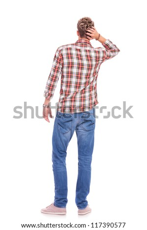 back view of a confused young casual man with his hand on the back of his head. isolated on white - stock photo