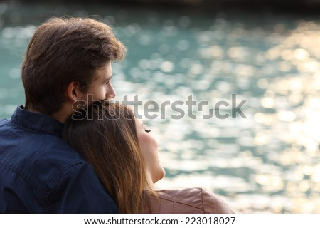 Back view of a couple hugging and watching the sea on the beach at sunset - stock photo