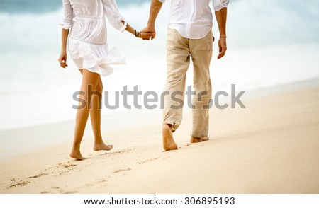 Back view of a couple taking a walk holding hands on the beach  - stock photo