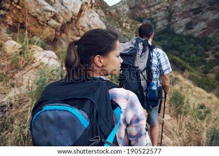 Back view of a couple walking along a hiking trail in the wilderness - stock photo