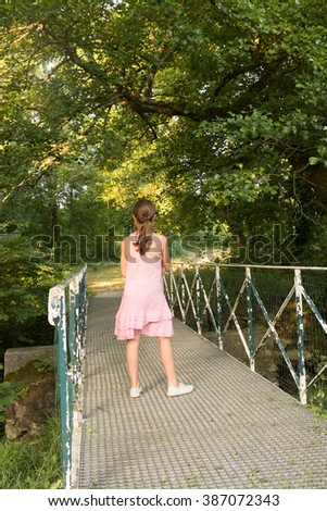 Back view of a cute girl walking on a bridge in a summer park after rain - stock photo