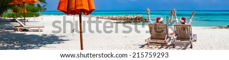 Back view of a happy couple in Santa hats relaxing on a tropical beach during Christmas vacation, panorama perfect for banners - stock photo