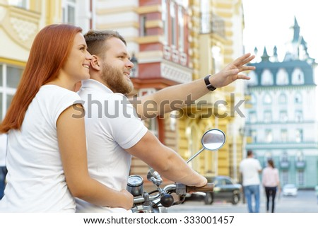 Back view of a happy couple sitting on a retro scooter while handsome bearded young man showing something to his red-haired girlfriend sitting behind him, in a European city - stock photo