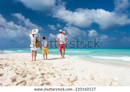Back view of a happy family on tropical beach - stock photo