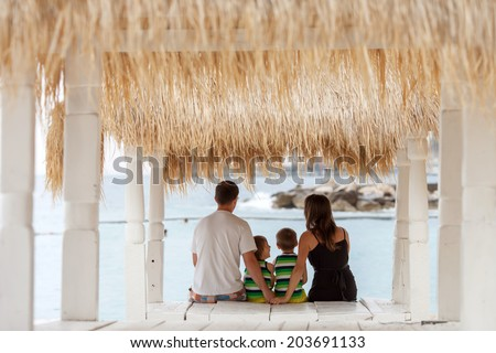 Back view of a happy family, sitting on the beach, watching the sea - stock photo