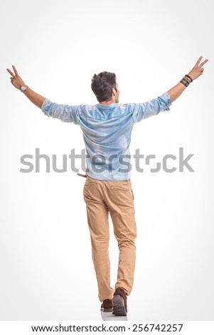 Back view of a happy young fashion man celebrating a victory while holding both hands in the air. - stock photo
