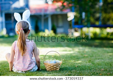 Back view of a  little girl wearing bunny ears with a basket of colorful Easter eggs outdoors on spring day - stock photo