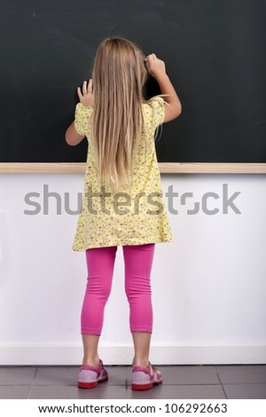 back view of a little girl writing on a chalkboard - stock photo