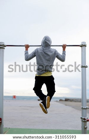 Back view of a male runner doing pull ups on the horizontal bar while training at evening outdoors, strong athlete in tracksuit doing exercise at street gym apparatus, young sportsmen playing sports  - stock photo