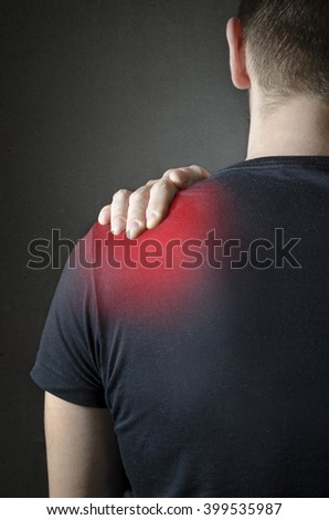 Back view of a Man with shoulder pain over dark background. Concept with highlighted glowing red spot. - stock photo