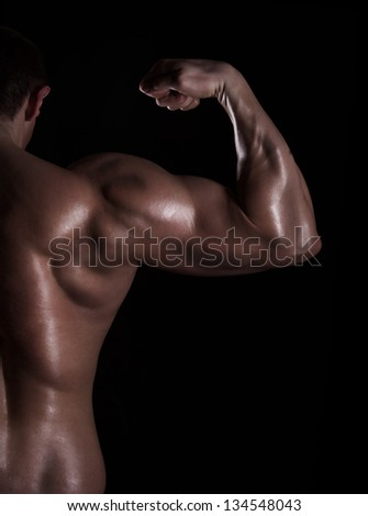 back view of a muscular young man showing his biceps isolated on black background - stock photo